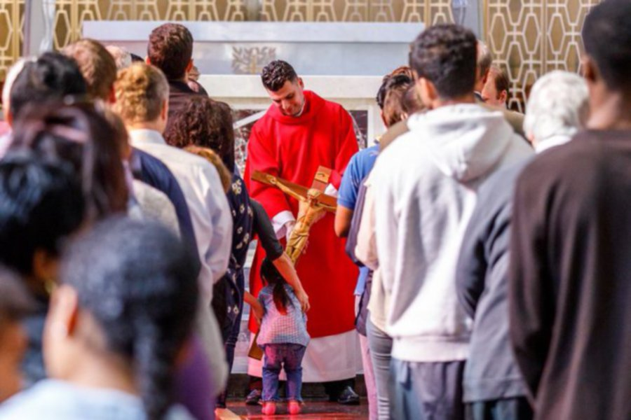 Father Anthony Federico holds a crucifix for  a young child during a service at St. Bridget Church.