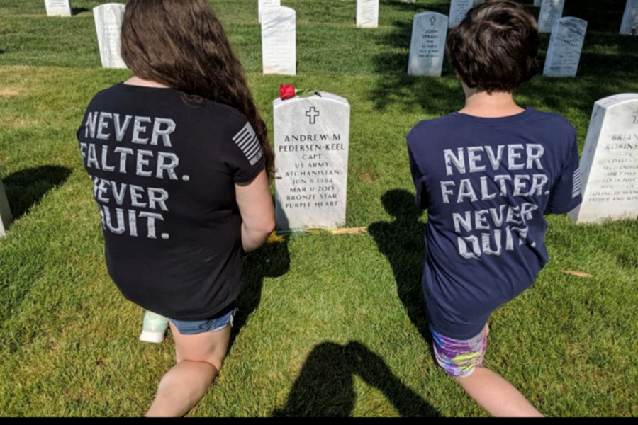 Hayley (left) and Jack Falk kneel at the gravesite of a soldier buried at Arlington National Cemetery.