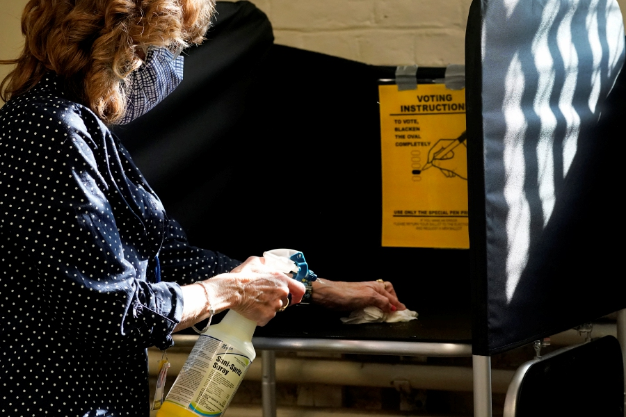 FILE - In this Oct. 22, 2020, file photo, election clerk Cheryl Lupi sanitizes a voting booth inside Haverhill City Hall during early in-person voting in Haverhill, Mass. The United States is approaching a record for the number of new daily coronavirus cases in the latest ominous sign about the disease