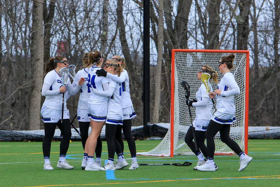 Wearing number 24, Annie Eddy is congratulated by her Colby lacrosse teammates after scoring a goal. Submitted photo.